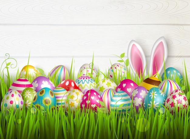 Composición de pascua con imágenes coloridas de festivos huevos de pascua en la superficie de la hierba verde con ilustración de orejas de conejo