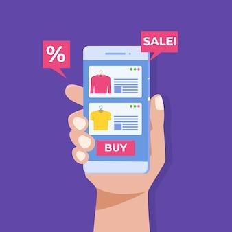 Compra de ropa en línea, mano que sostiene el teléfono inteligente, marketing digital.