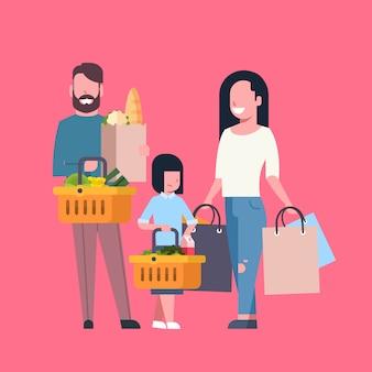 Compras de la familia joven con bolsa de papel y cesta llena de productos comestibles