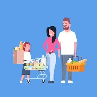 Compras de la familia joven que sostienen la bolsa de papel, el carro y la cesta llenos de productos comestibles