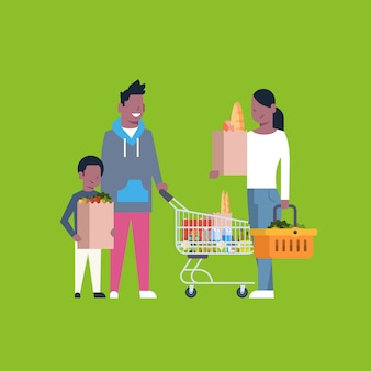 Compras familiares afroamericanas con bolsa de papel, carrito y canasta llenos de productos comestibles