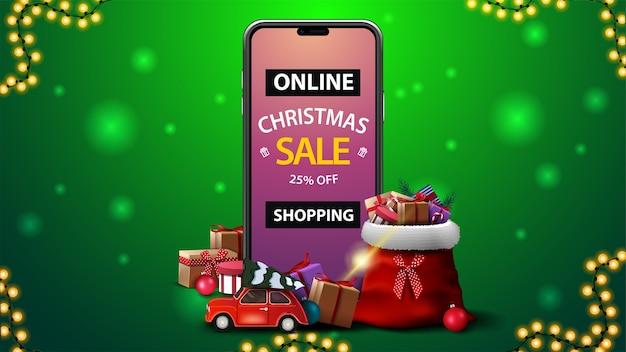 Compras en línea, venta de navidad, banner de descuento verde con teléfono inteligente con oferta en pantalla, bolsa de papá noel con regalos y auto antiguo rojo con árbol de navidad