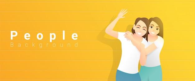 Concepto de amistad con dos jóvenes mujeres felices abrazándose y de pie en amarillo