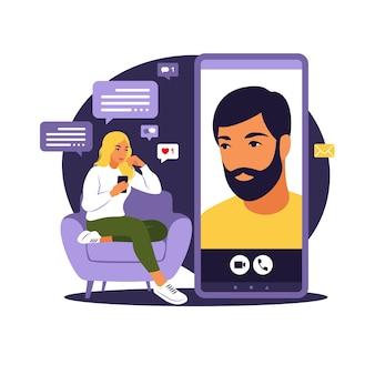 Concepto de aplicación, aplicación o chat de citas. la mujer está sentada con un gran teléfono inteligente en el sofá y hablando por teléfono.