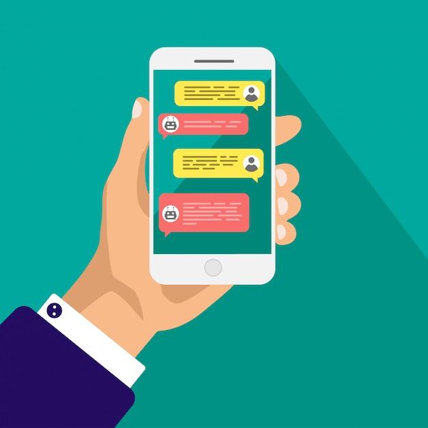 Concepto de chat bot. la mano sostiene el teléfono inteligente con cuadros de diálogo.