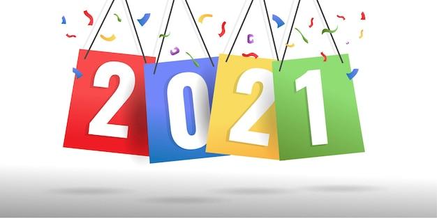 Concepto creativo de feliz año nuevo 2021 en papel de colores colgantes.