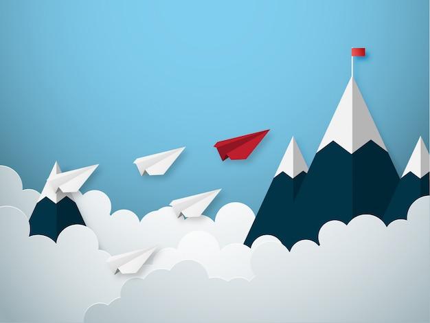 El concepto de la dirección con el papel rojo y blanco corta el aeroplano del estilo que vuela a la bandera de la meta en la montaña.