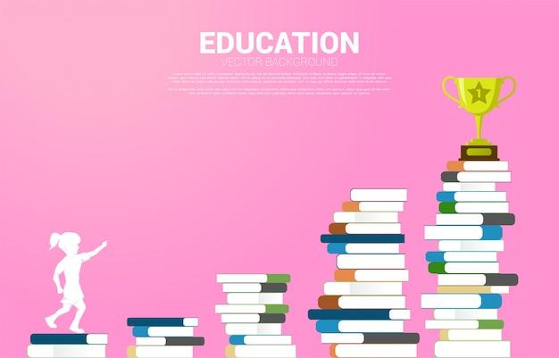 Concepto educación y niños. la silueta de la muchacha mira para arriba al trofeo en la pila de libros.