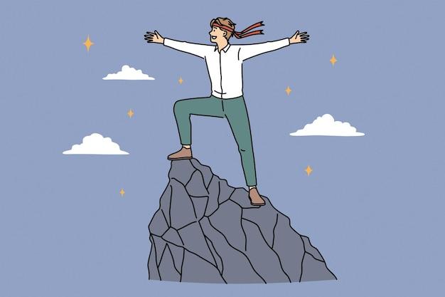 Concepto de éxito, desarrollo y logro empresarial. joven empresario sonriente personaje de dibujos animados de pie en la cima de la montaña sintiéndose seguro de libertad ilustración vectorial