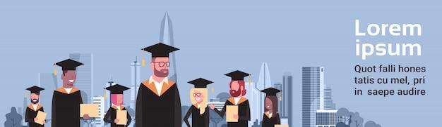 Concepto de graduación grupo de estudiantes de raza mixta en toga y bata diploma sobre la ciudad moderna