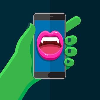 Concepto de halloween. mano verde sosteniendo un teléfono con boca de vampiro hablando con labios rojos abiertos y colmillos en la pantalla.