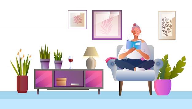 Concepto interior de vector con mujer joven sentada en un sillón leyendo un libro.