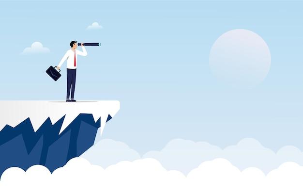 Concepto de negocio con empresario sosteniendo telescopio de pie sobre un símbolo de acantilado.