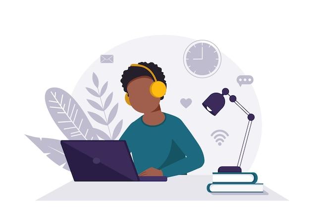 Concepto de oficina en casa, hombre negro con auriculares y portátil trabajando desde casa, estudiante o autónomo.