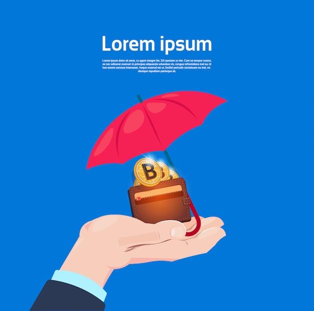 Concepto de protección del servicio de seguro asimiento de la mano bitcoin billetera paraguas criptomoneda protectora sobre fondo azul espacio de copia plana