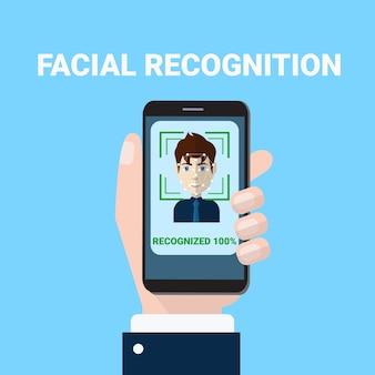 Concepto de reconocimiento facial de la mano que sostiene la exploración de smartphone de la biometría de rostro masculino