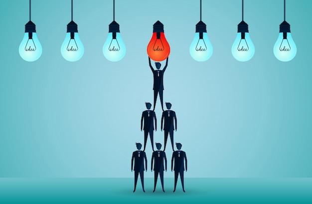 Concepto de trabajo en equipo de negocios. hombres de negocios de pie uno sobre el otro levantando la bombilla roja hacia arriba. armonioso. idea creativa