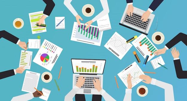 Concepto de trabajo en equipo. vista de escritorio de oficina superior de lluvia de ideas, reunión de negocios. manos con ilustración de documentos y computadoras portátiles