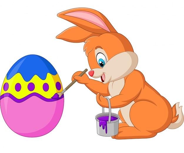 Conejito de pascua pintando un huevo