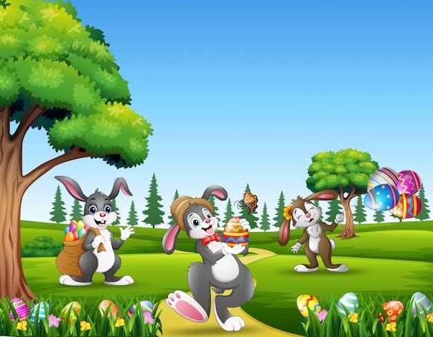 Conejitos de dibujos animados con huevos decorados sobre fondo de pascua