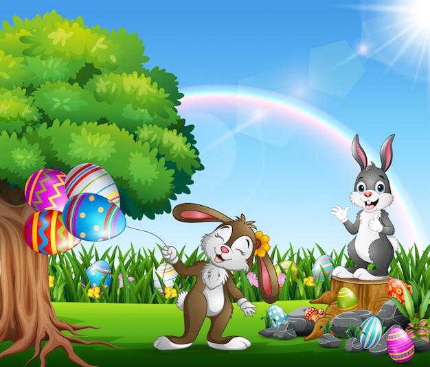 Conejitos de pascua y huevos coloridos en el jardín.