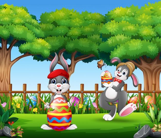 Conejitos de pascua sosteniendo un huevo decorado colorido