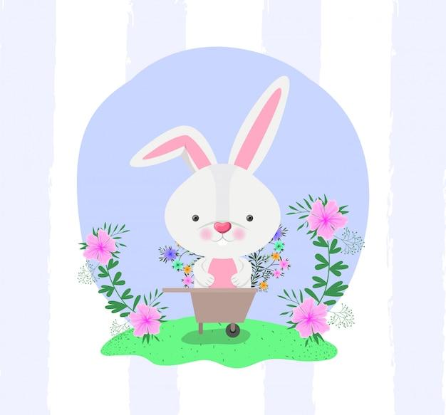 Conejo y carretilla con flores en el jardín.
