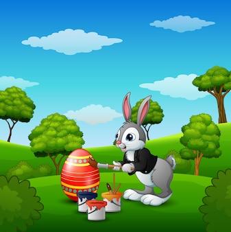 Conejo de pascua pintando huevos de pascua en el parque