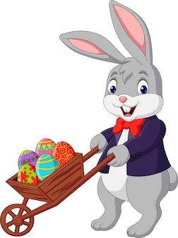 Conejo de dibujos animados empujando el carrito lleno de huevos de pascua