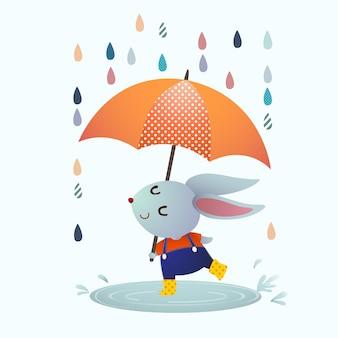 Conejo gris de dibujos animados chapoteando en un charco en un día lluvioso.