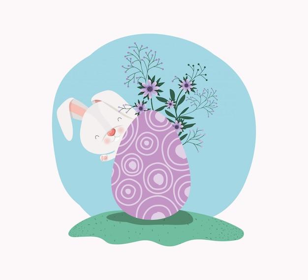 Conejo lindo con huevo pintado y flores en el jardín.