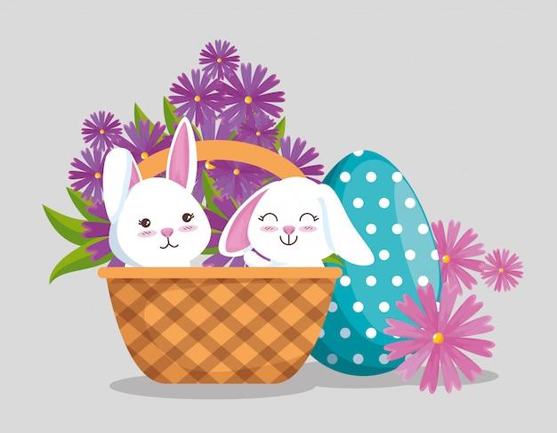 Conejos dentro de la canasta con decoración de huevos y flores.