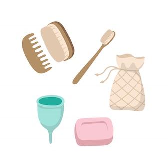 Conjunto de artículos de higiene personal ecológicos: cepillo de dientes de madera, copa menstrual, jabón sólido, cepillos, bolsa de algodón.