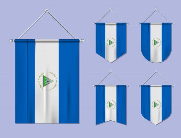 Conjunto de banderas colgantes nicaragua con textura textil. formas de diversidad del país de bandera nacional. banderín de plantilla vertical