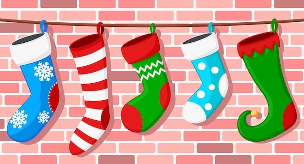 Un conjunto de calcetines navideños cuelga de una cuerda contra una pared de ladrillos.