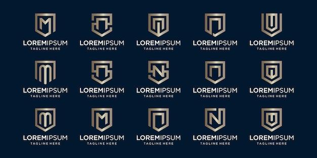 Conjunto de combinación de signo de escudo y monograma de letra mnv.