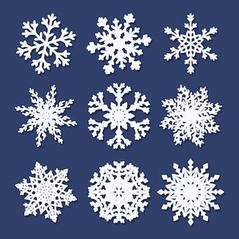 Conjunto de copos de nieve de papel blanco aislado sobre fondo azul.
