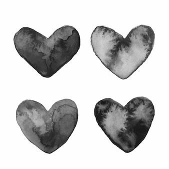 Conjunto de cuatro corazones pintados en acuarela negra con manchas