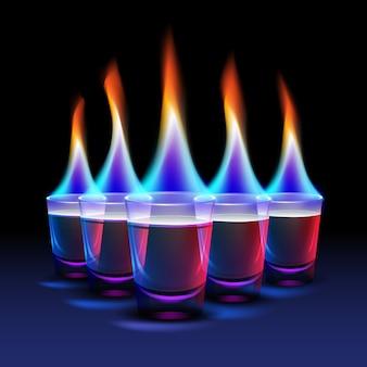 Conjunto de disparos de cóctel ardiente con fuego de color y luz de fondo azul, roja aislada sobre fondo negro