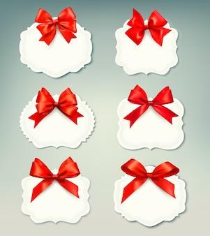 Conjunto de hermosas etiquetas retro con arcos de regalo rojos con cintas.
