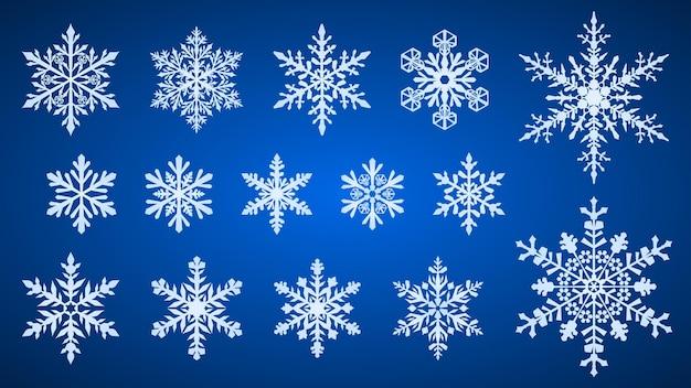 Conjunto de hermosos copos de nieve de navidad complejos, blancos sobre fondo azul.