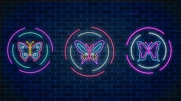 Conjunto de letreros de neón brillantes de mariposa en marcos redondos en la pared de ladrillo oscuro