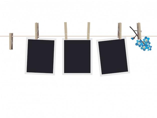 Conjunto de marcos de fotos en blanco colgando de pinzas para la ropa