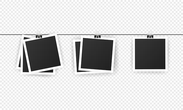 Conjunto de marcos de fotos instantáneos en blanco colgando de un clip