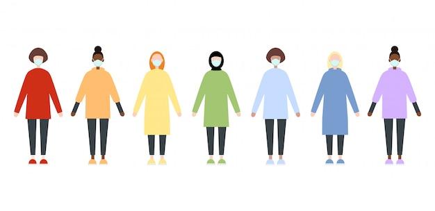 Conjunto de mujeres de raza diversa en ropa de arco iris con máscaras. la enfermera friega la ropa. estilo plano