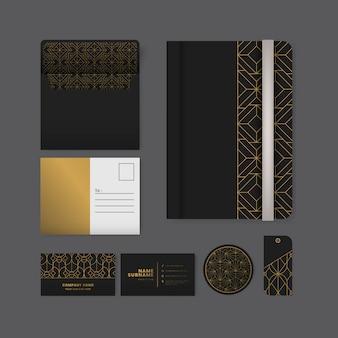 Conjunto de patrón geométrico dorado en papelería de superficie negra