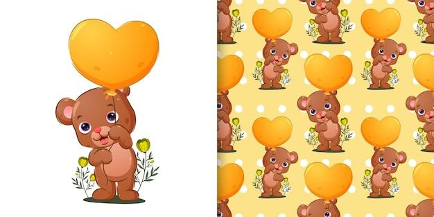El conjunto de patrones del oso sostiene el globo de colores brillantes.