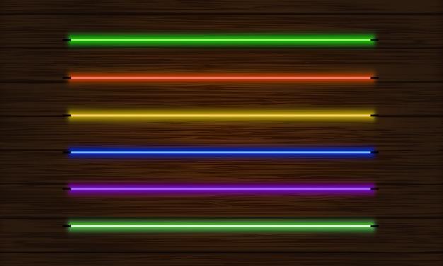 Conjunto de pinceles de neón. conjunto de objetos de luz de colores sobre un fondo oscuro del árbol.
