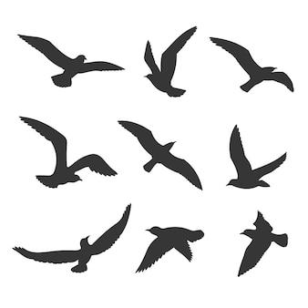 Conjunto de silueta de pájaros volando