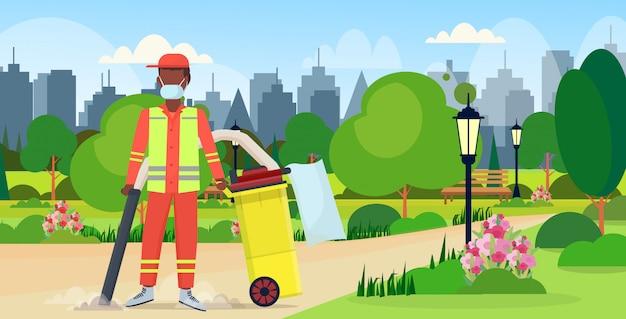 Conserje callejero masculino con aspiradora profesional hombre afroamericano aspirar basura servicio de limpieza concepto parque urbano paisaje urbano fondo plano horizontal horizontal